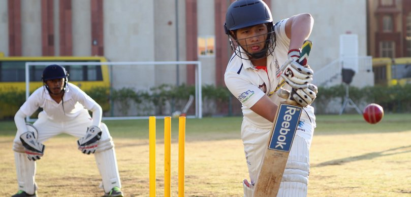 Image showing a young man playing cricket and moving in towards the ball with hiss bat at the Indian High School in Dubai