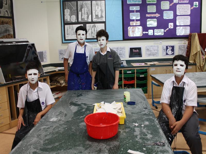 Ang mga matatandang bata na malikhaing gumagawa ng mga maskara ng Papier-mâché sa Al Bateen Academy sa Abu Dhabi