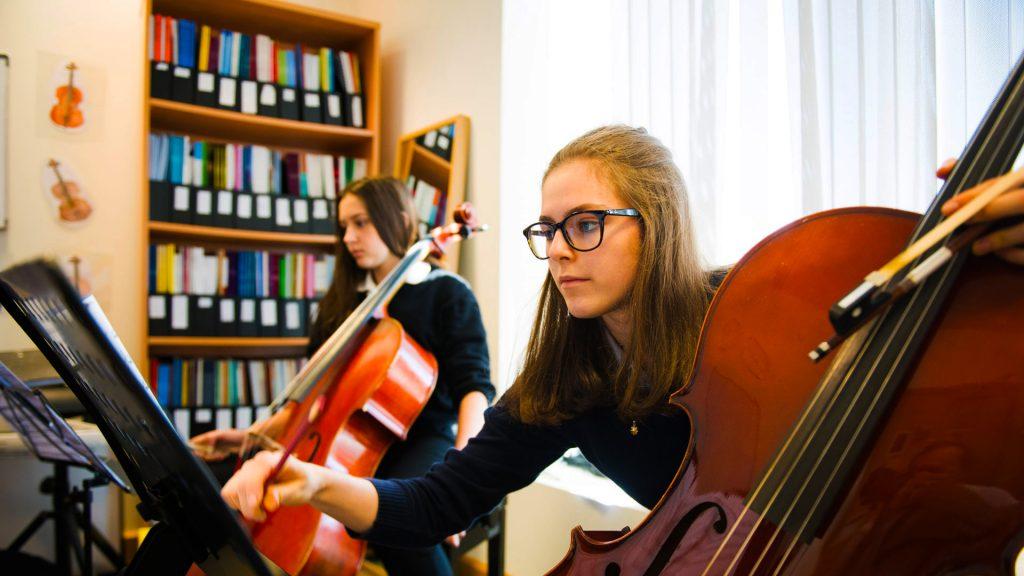 Kuha ng larawan na nagpapakita ng mga kabataang babae sa The British School Al Khubairat na naglalaro ng kanilang mga instrumento sa isang klase ng Musika
