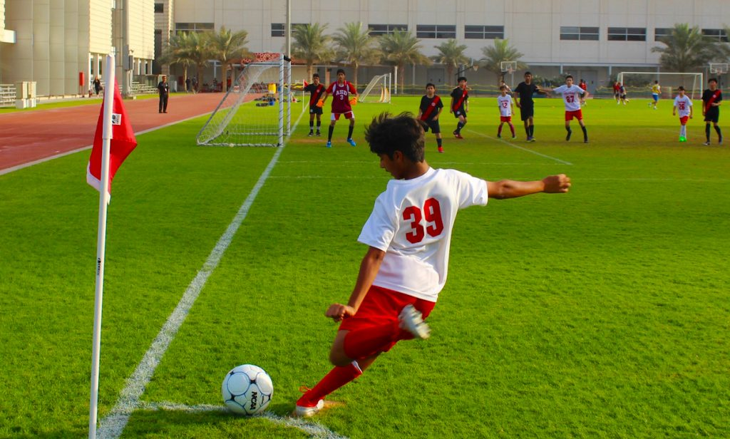 Football at the American School of Dubai picturing a young boy taking a corner with team members waiting for the ball to cross the goal