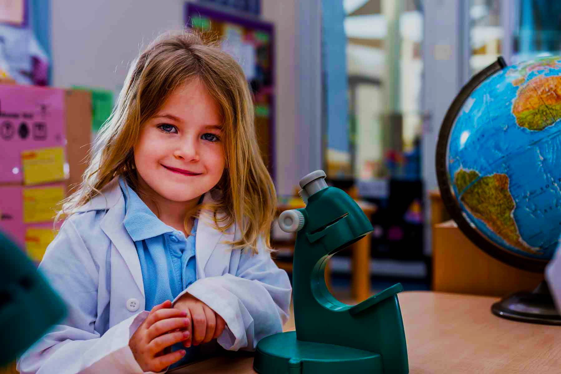 Photograph of young girl at Uptown School in the labs with a microscope looking happy and inspired