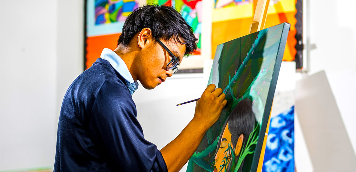 Photograph of an accomplished Art student at Uptown School in Dubai working with acrylic portraiture