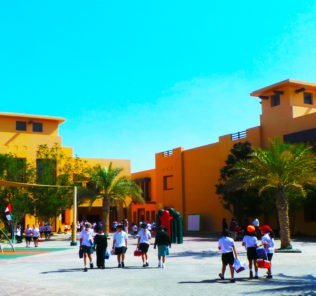 Raha International School building entrance with children leaving and entering the main reception