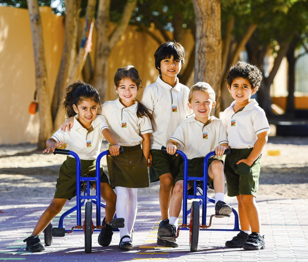 Photograph of young children at Greenfield Community School in woodland, two of them on tricycles