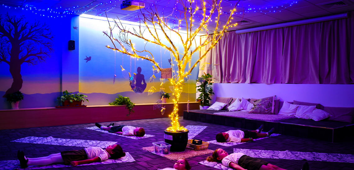 Photograph of the beautiful, purple colour-washed Mindfulness Room at Greenfield Community School with children peacefully looking at the moving colours and golden lit tree in the centre