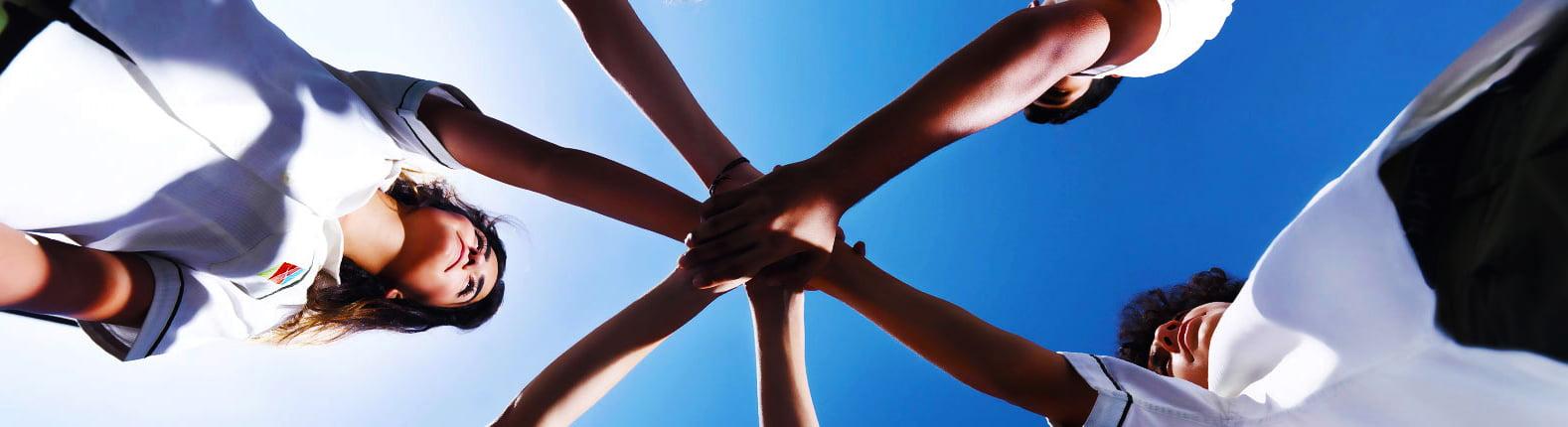 Anspruchsbild, das Kinder an der Greenfield Community School zeigt, die Hände mit dem Himmel im Hintergrund halten