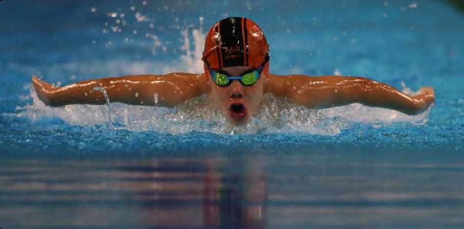 Junger Mann, der an der Greenfield Community School in Dubai schwimmt und seine Fähigkeiten bei Butterfly zeigt