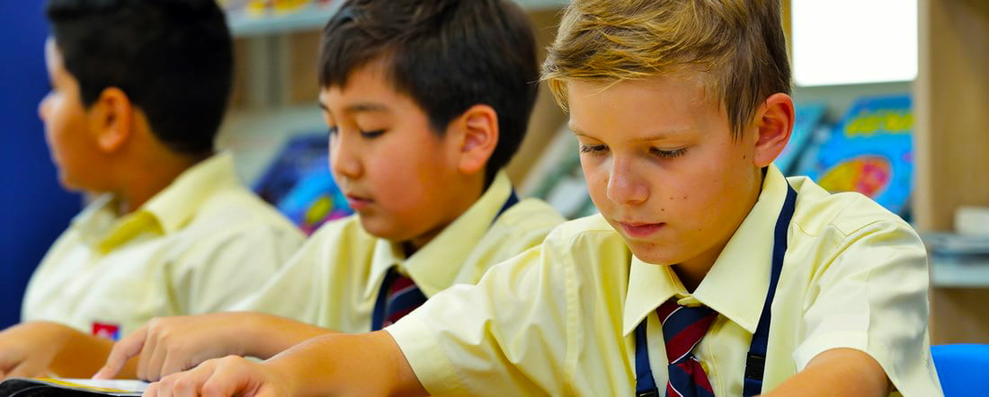 Photograph of boys absorbed in studying during a lesson at GEMS Founders School in Dubai