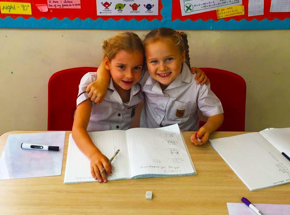 Foto von zwei kleinen Kindern an der Victory Heights Primary School in Dubai, die zusammen lernen und sich gegenseitig helfen, einen Auftrag zu erfüllen