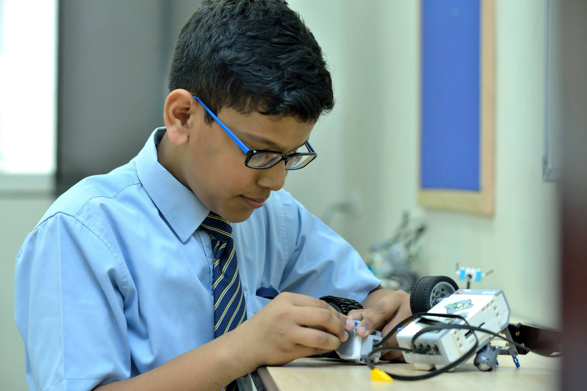 صورة فوتوغرافية لطالب في مدرسة GEMS Heritage الهندية في دبي يشارك في الدراسة مع LEGO Robotics كجزء من منهج STEM المعزز