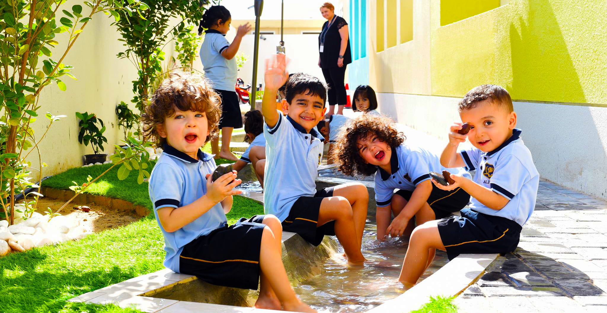 Photograph of children at The Alpha School in Dubai engaged in learning activities outside with water