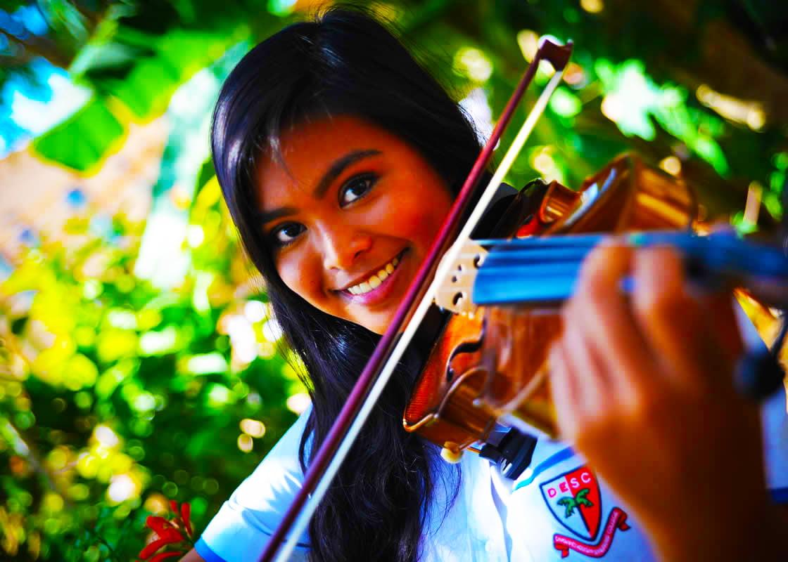 الثقافة في مدرسة دبي للتخاطب بالإنجليزية DESS هي الاحتفال بالعديد من الهدايا المختلفة للأطفال الأفراد. تظهر هذه الصورة فتاة صغيرة تطور مواهبها الموسيقية تعزف على الكمان.