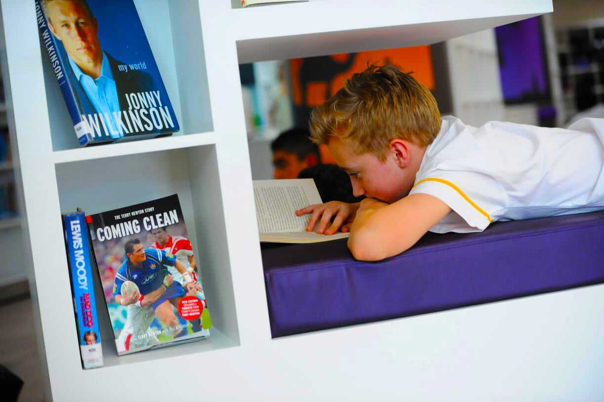 Photograph of a student reading in the new library at Dubai English Speaking School DESC