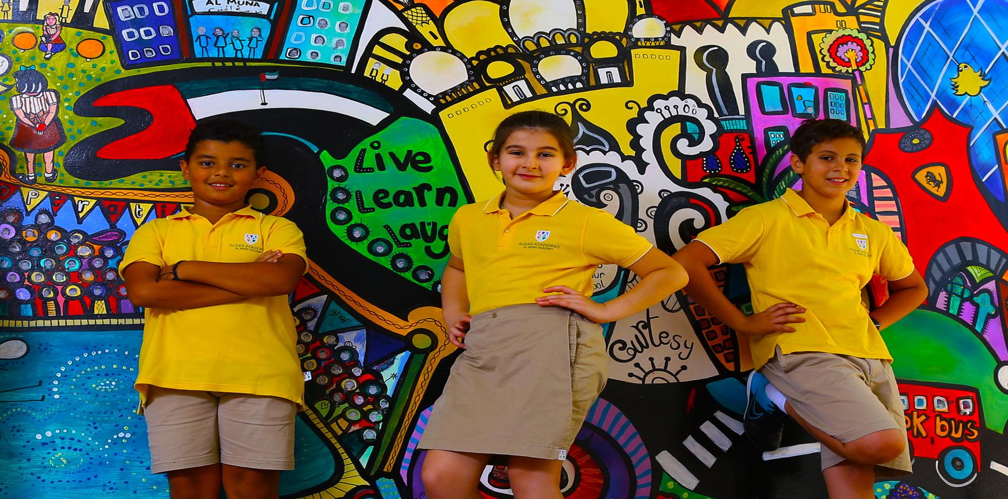Ang mga bata sa Al Muna Primary School sa Abu Dhabi ay buong kapurihan na nakatayo sa harap ng isang pader ng graffiti na kanilang nilikha
