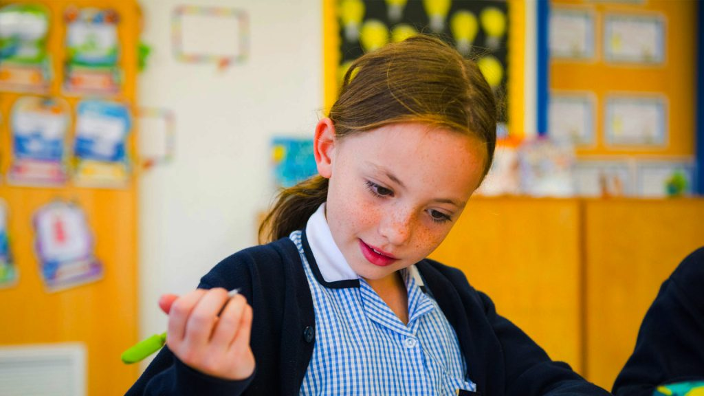 Photo of Primary Phase girl in a SEND class learning how to write
