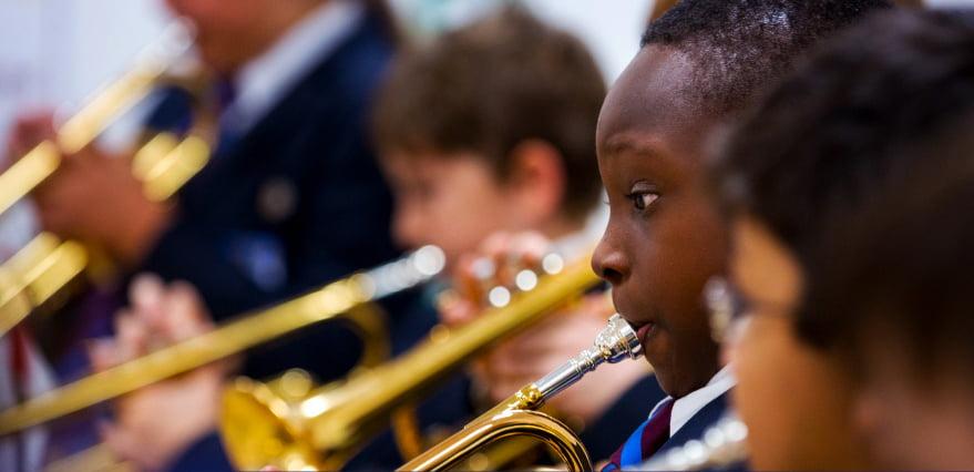 Ang larawan na nakatuon sa musika sa Brighton College Abu Dhabi na nagpapakita ng isang bata na naglalaro ng kanyang puso gamit ang isang trumpeta sa orkestra