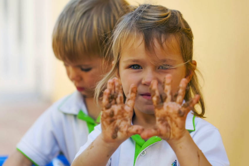 Image of younger children at Jebel Ali School getting their hands dirty during outside play session devloping fine motor skills - awarded one of the top 20 Best Schools in Dubai and Abu Dhabi by schoolscompared.com in 2017