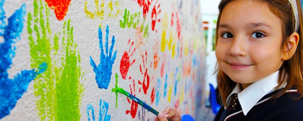 Isang imahe ng isang batang babae na may pintura sa GEMS Wellington Primary School sa Dubai