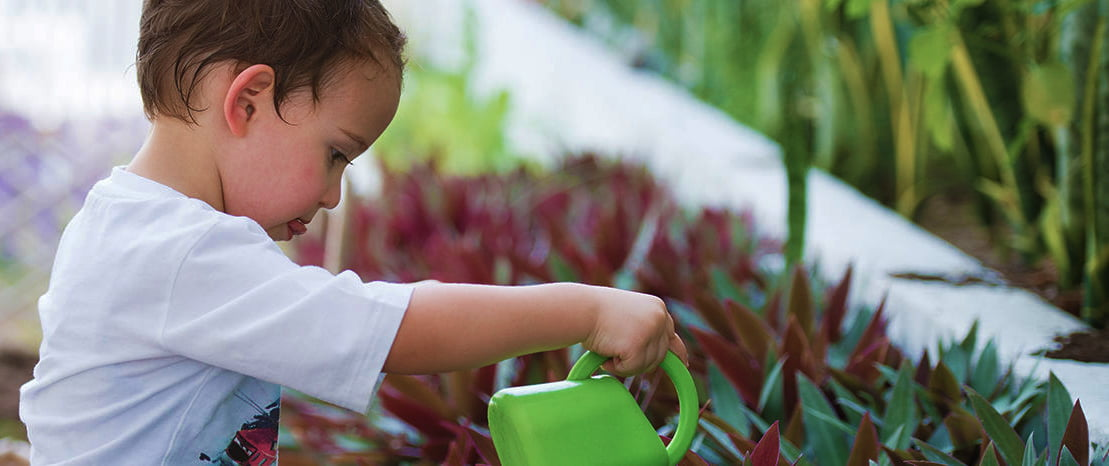 Child with watering can highlighting the sustainability and environmental credentials of Fairgreen International School Dubai