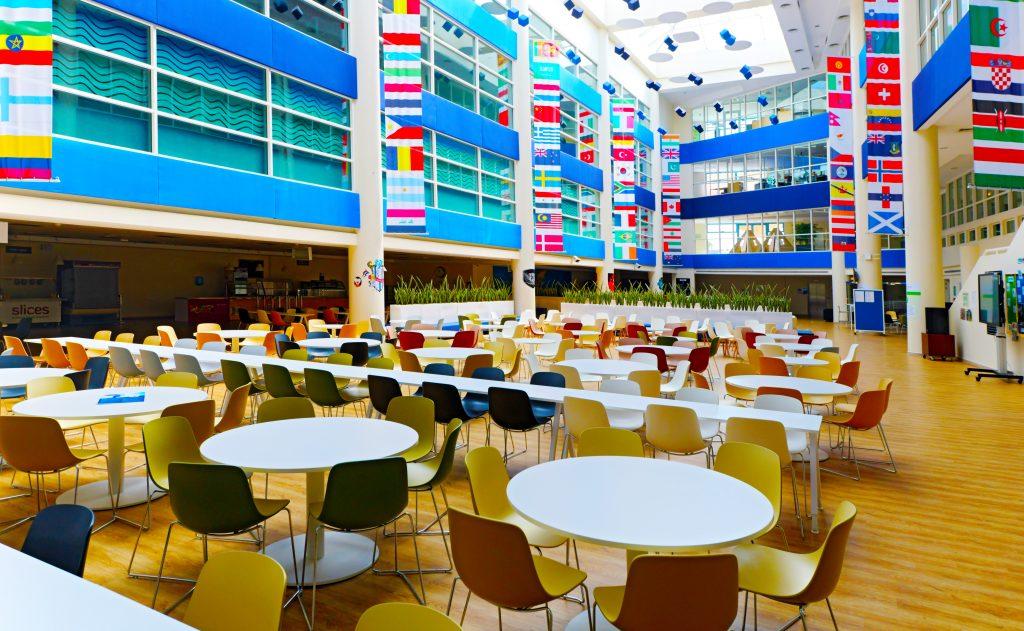 Kunan ng larawan ng naayos na bagong sentral na karinderya sa gitnang baso na may ilaw na awditoryum ng GEMS Wellington International School sa Dubai na kinunan noong 2021