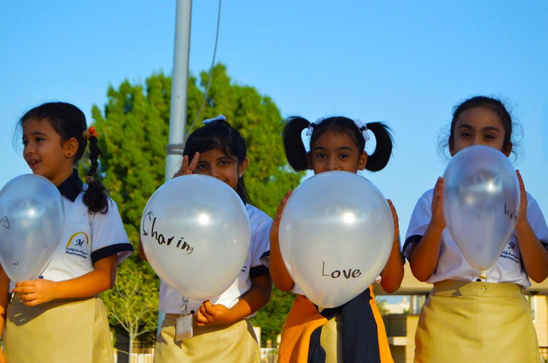 Isang imahe ng mga bata na gumagamit ng mga lobo upang malaman ang tungkol sa wika sa Mirdif Private School sa Dubai