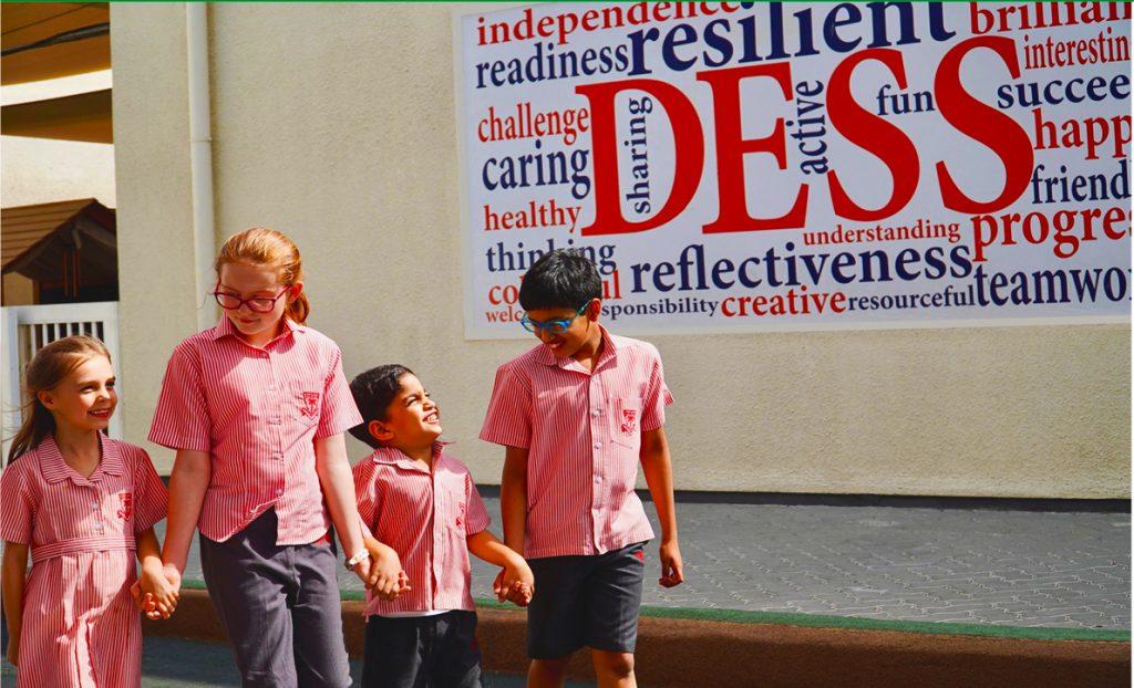 أطفال يمسكون أيديهم في مدرسة دبي للتخاطب بالإنجليزية DESS في دبي بجوار لافتة تسلط الضوء على قيم المدرسة التي تشمل الرعاية والإبداع والانعكاس