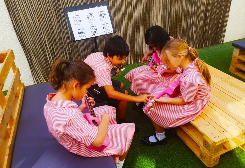 صورة لأطفال يتعلمون الجيتار في فصول الموسيقى الخارجية في مدرسة دبي للناطقين بالإنجليزية DESS في دبي