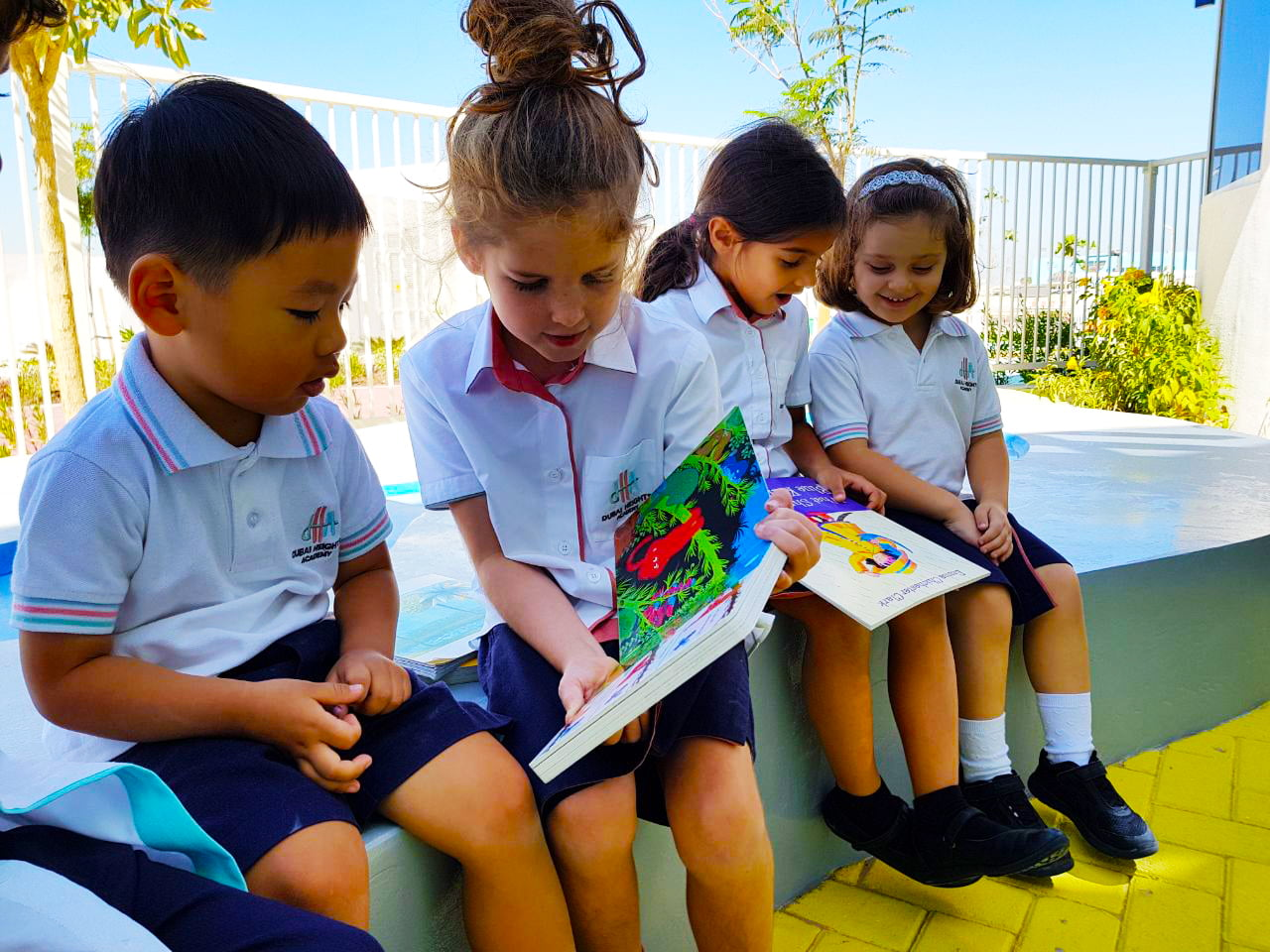 Children reading in the grounds of Dubai Heights Academy