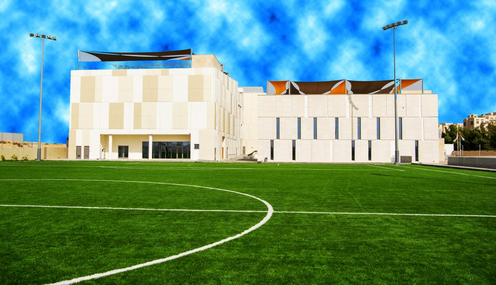 Photograph of the full sized sports fields looking on to the main school building at South View School in Dubai