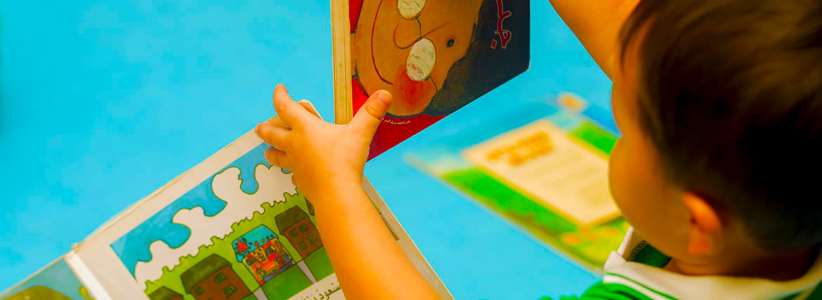 Best nursery schools in the UAE including Dubai and Abu Dhabi - image shows young child reading and exploring with pictures