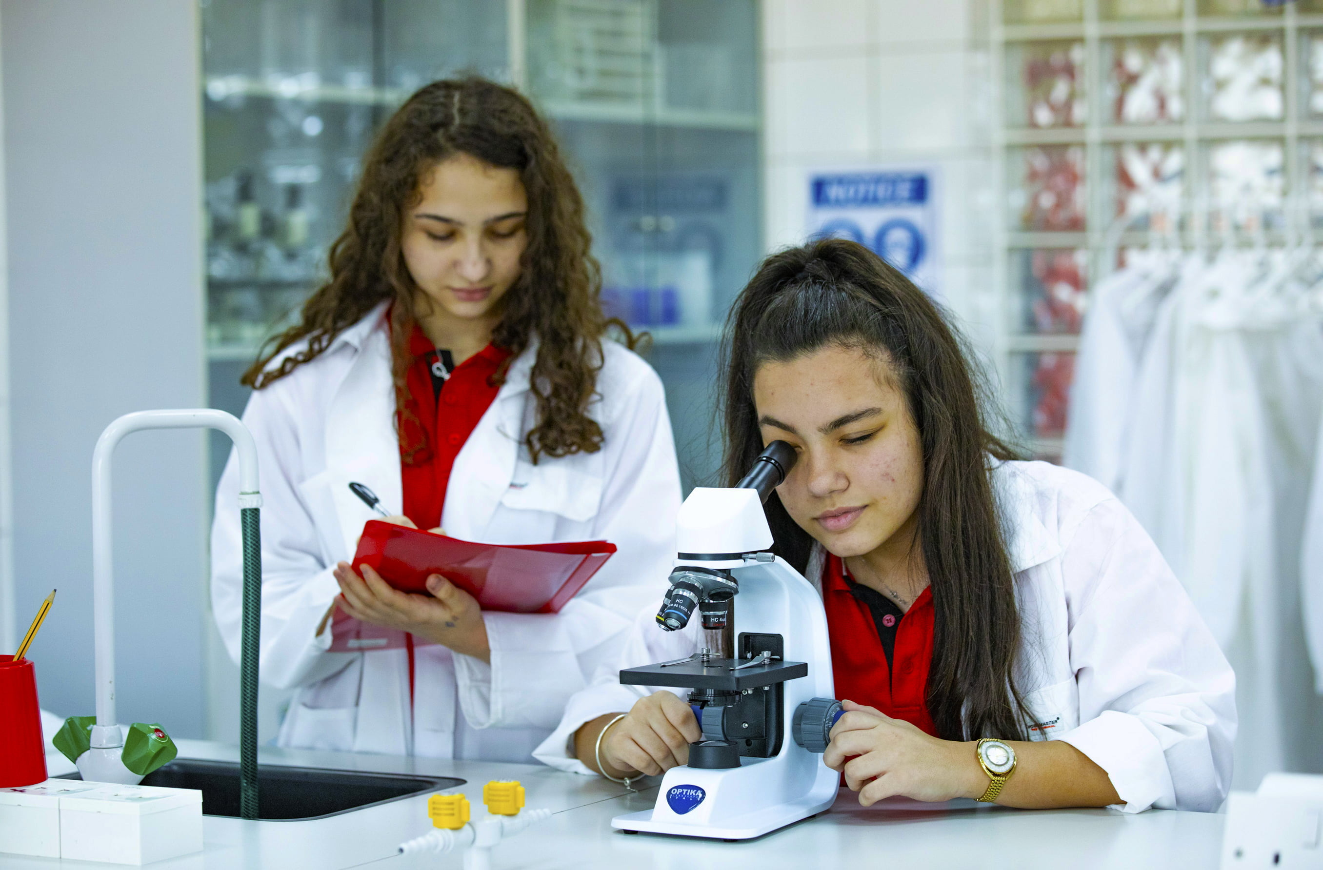 Students engaged in STEM and Science at Ontario International Canadian School in Dubai using a microscope in the dedicated labs facilities