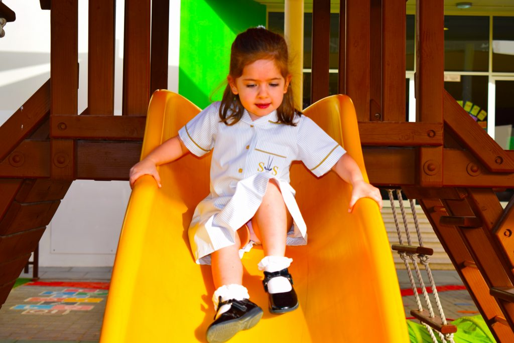 Young student on a slide at South View School in Dubai. The school has invested heavily in outdoor play equipment for children to develop motoring skills and balance formal classroom based teaching of the EYFS curriculum.