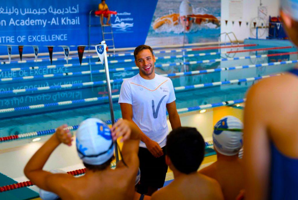 صورة لأكاديمية جيمس ويلينجتون ، مركز الخيل المتخصص للتميز - أكاديمية تدريب متخصصة فريدة للسباحة في دبي. في الصورة نرى سباح البطل الأولمبي والعالمي وألعاب الكومنولث في جنوب أفريقيا ، تشاد لو كلوس ، يتحدث مع طلاب منحة النخبة في المدرسة.