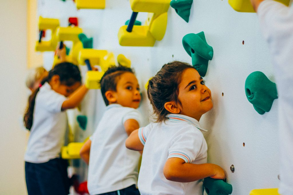 Photograpg of children using the climbing wall at Dubai Heights Academy in Dubai