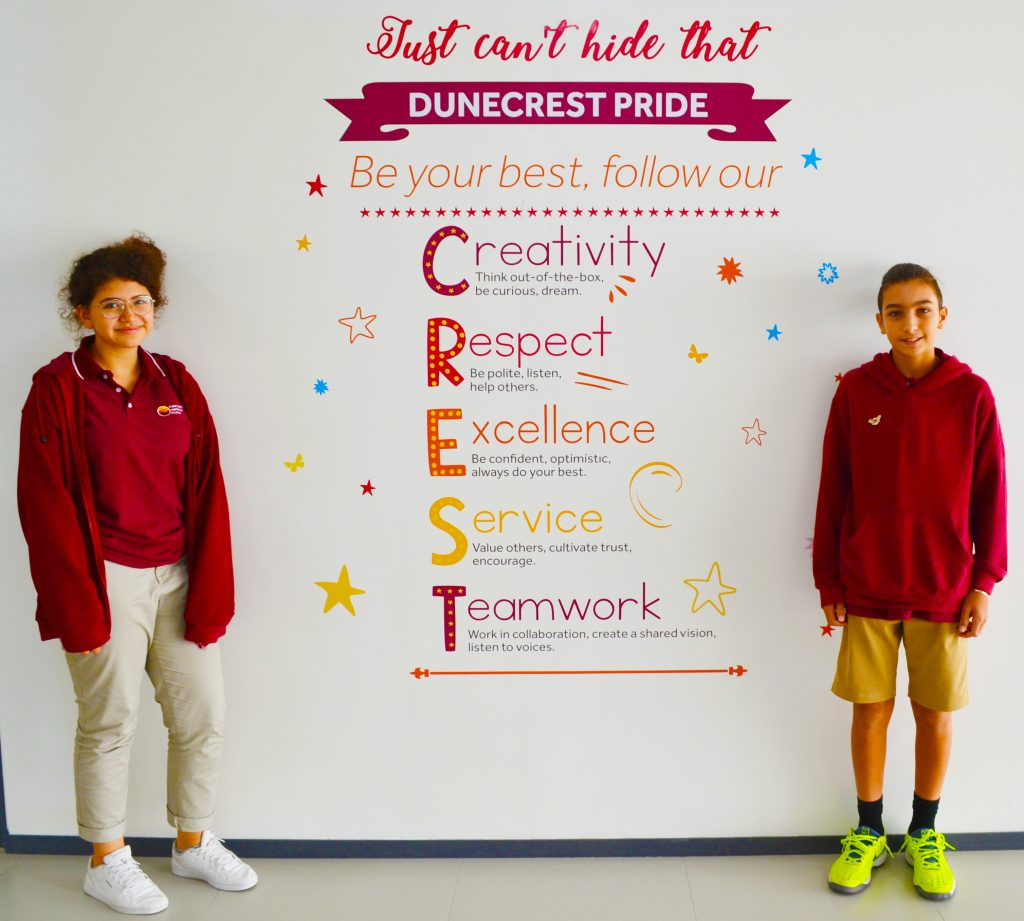 Photograph of two children at Dunecrest American School in Dubai celebrating the school values that are published at the heart of the school