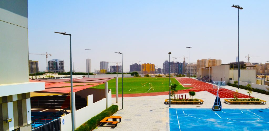 Photograph showing the buildings and sporting grounds of Dunecrest American School set against the Dubai skyline
