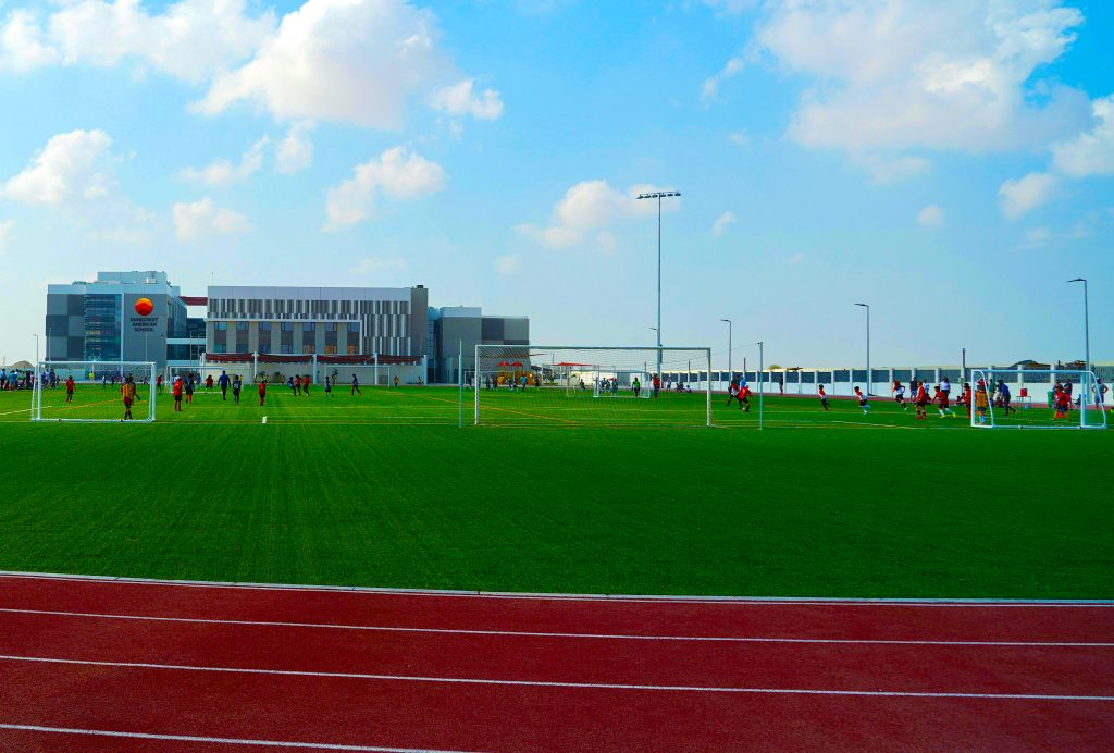 Photograph highlighting the extensive Sport facilities at Dunecrest American School in Dubai. These are sown in the foreground with the main school buildings in the background to give an idea of scale.