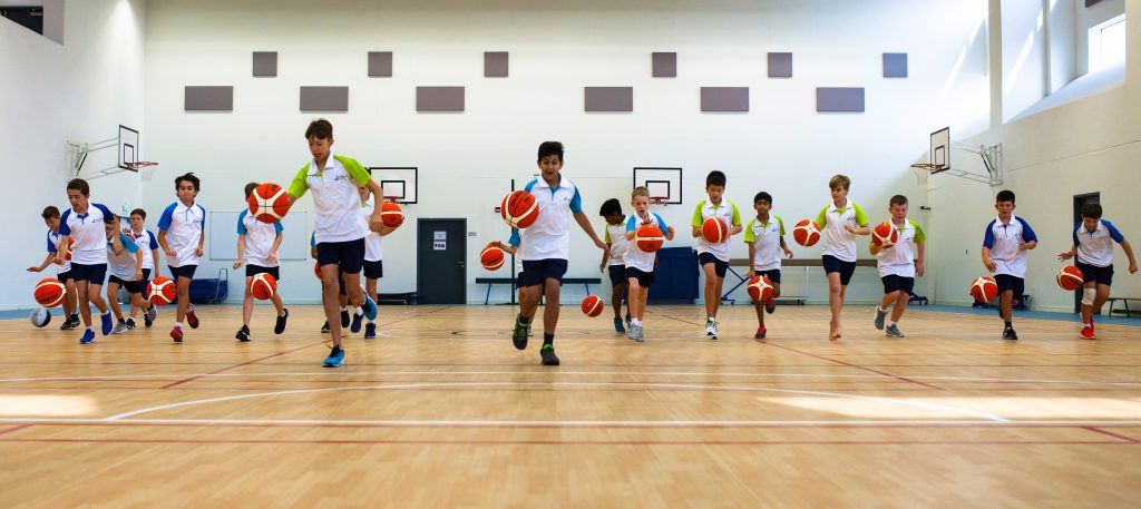 Photograph of the main Sports Hall and children playing basketball at the Jebel Ali School in Dubai.