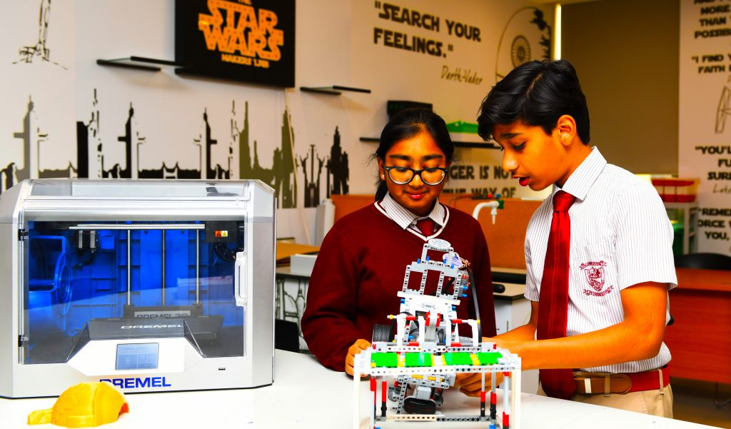 Photograph of male and female students engaged in LEGO Robotics as part of the technology curriculum and enhanced ECA Programme at GEMS New Millennium School in Dubai