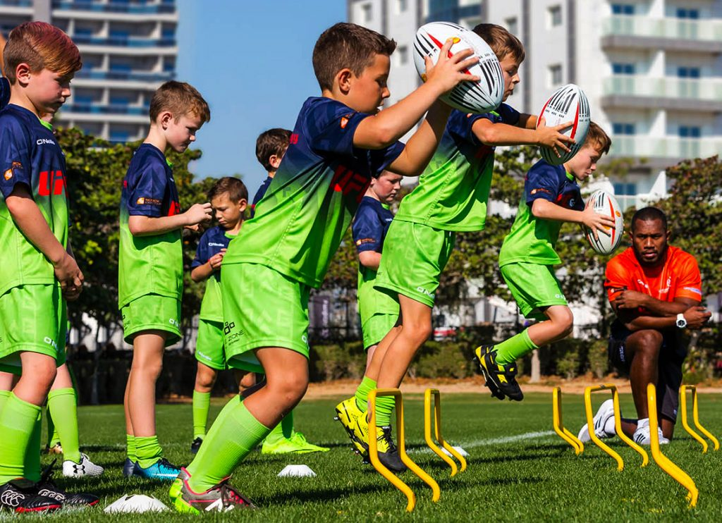 Schools Out! Top 25 Guide to What's On and What to Do in the Summer Holidays. Here children at the Apollo Perelini Summer Holiday camp practice their jumping and running with the rugby ball skills in team trials.
