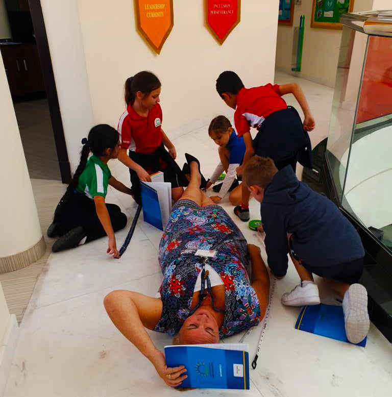 Photograph of Rachael Wilding, Principal of Smart Vision School in Dubai engaging with Primary children to bring English National Curriculum learning to life.