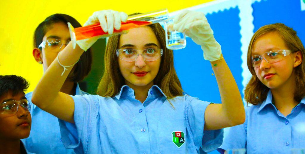 Larawan ng mga bata sa Dubai International Academy Al Barsha na nakikibahagi sa isang eksperimento sa kimika bilang bahagi ng pag-aaral ng Agham para sa International Baccalaureate