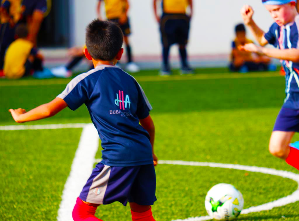 Photograpg of child playing competeitive football at Dubai Heights Academy school in Dubai