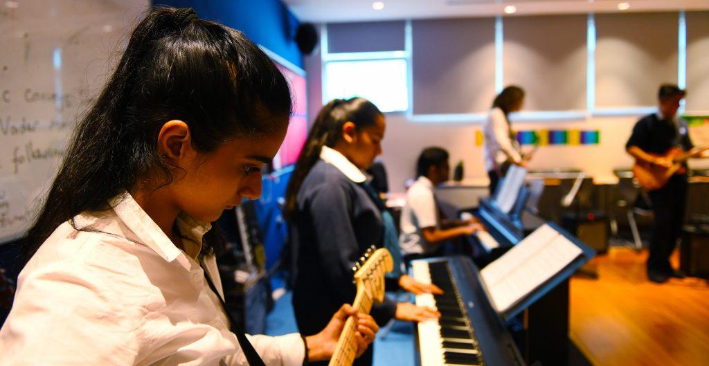 Foto der Bandpraxis an der GEMS Wellington Academy Dubai Silicon Oasis mit Schülern, die an Gitarre, Keyboards, Klavier, akustischer und elektrischer Gitarre spielen