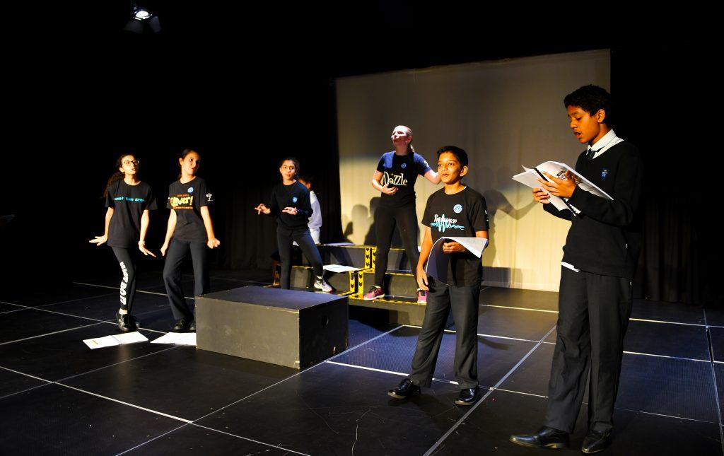 Foto von Schauspielstudenten der GEMS Wellington Academy Dubai Silicon Oasis, die sich auf eine große Aufführung im Black Box Theatre der Schule vorbereiten.
