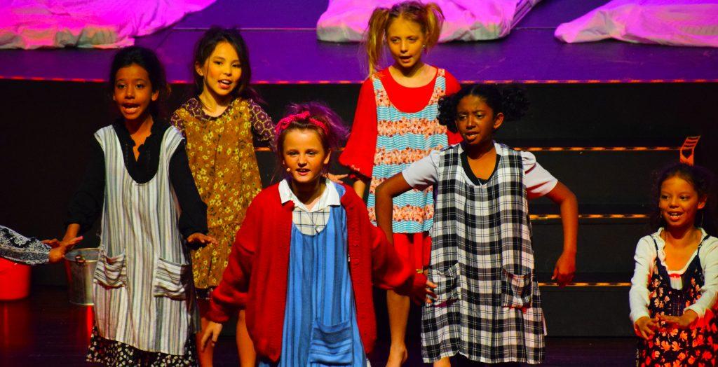 Foto von Studenten, die live auf der Bühne bei der Musiktheateraufführung von Annie in der GEMS Wellington Academy Dubai Silicon Oasis auftreten.