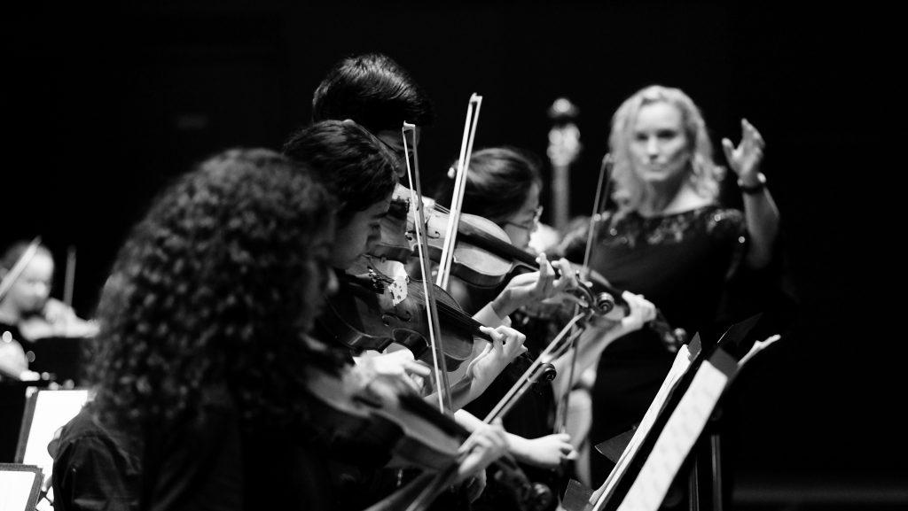 Foto von Musikwissenschaftlern am Dubai College, die Geige in einer wegweisenden Orchesterproduktion im Auditorium mit 1000 Plätzen spielen