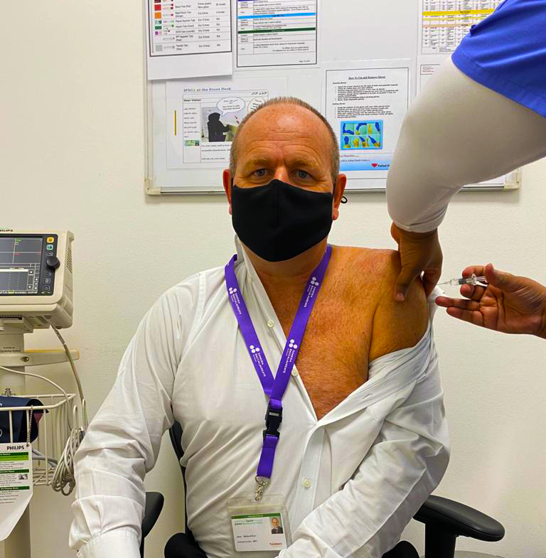 Photograph of Richard Drew, Principal, Jumeira Baccalaureate School in Dubai receiving the Covid 19 vaccine in February 2021 to protecxt his school and students from the virus
