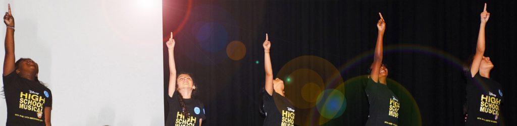 Foto von Schülern, die beim großen Finale der musikalischen Produktion von High School Musical an der GEMS Wellington Academy in Dubai Silicon Oasis auftreten. Das Publikum spürt ein spürbares Gefühl des Triumphs.