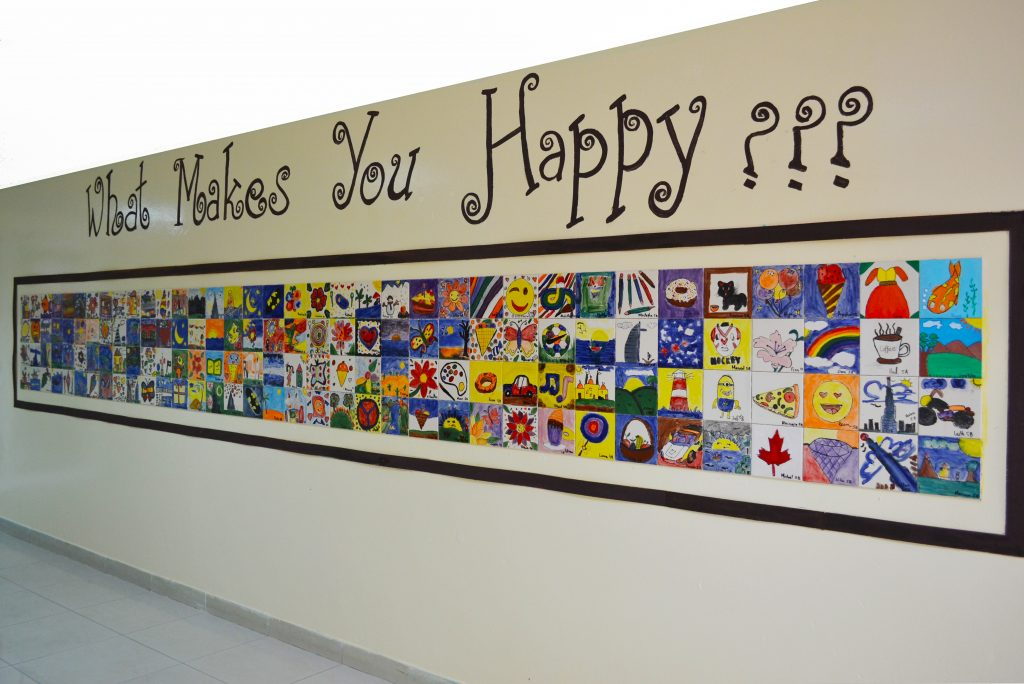 A wall showing student's work in Fine Arts at North American International School in Dubai. The wall is comprised of hand drawn and painted ceramic tiles.